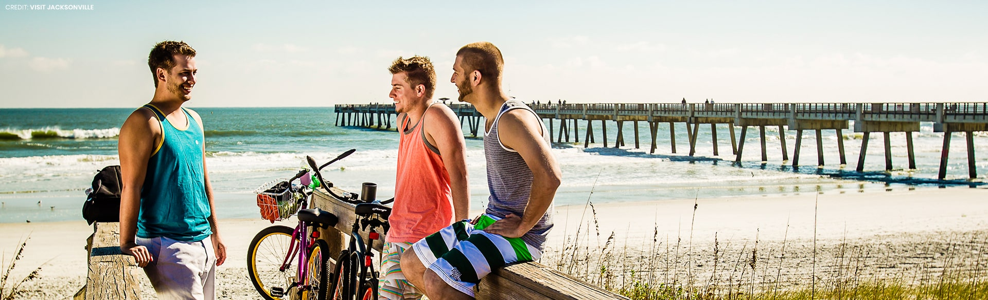 3 guys talking on boardwalk on the beach with pier in background