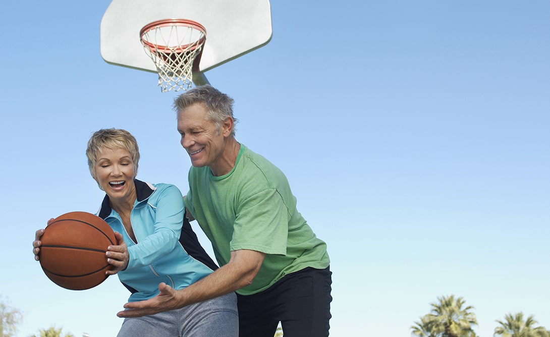 older couple playing basketball at tributary