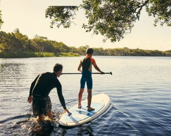 Father son paddle boarding on river