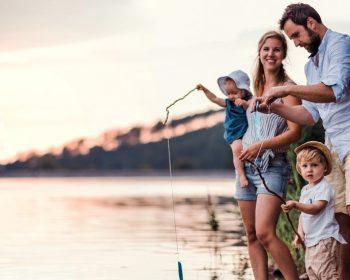 Tributary family fishing on river shoreline