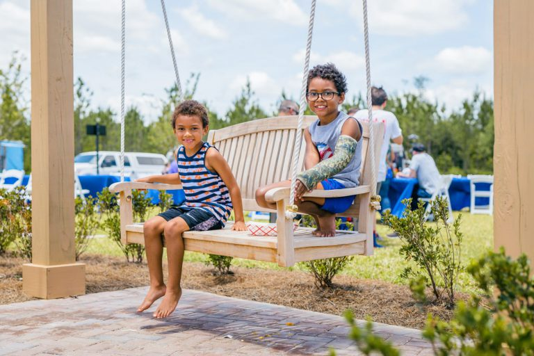 2 kids smiling on swing at the Tributary Model Home Event park