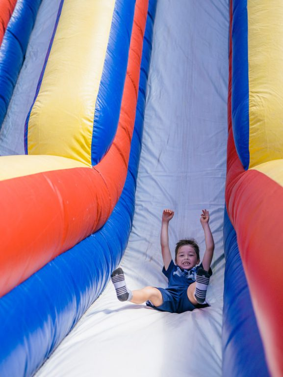 kid smiling down a slide at Tributary Model Home Event