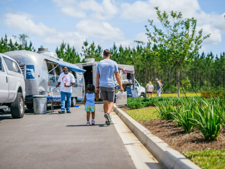 father and daughter walking to food trucks at Tributary Model Home Event