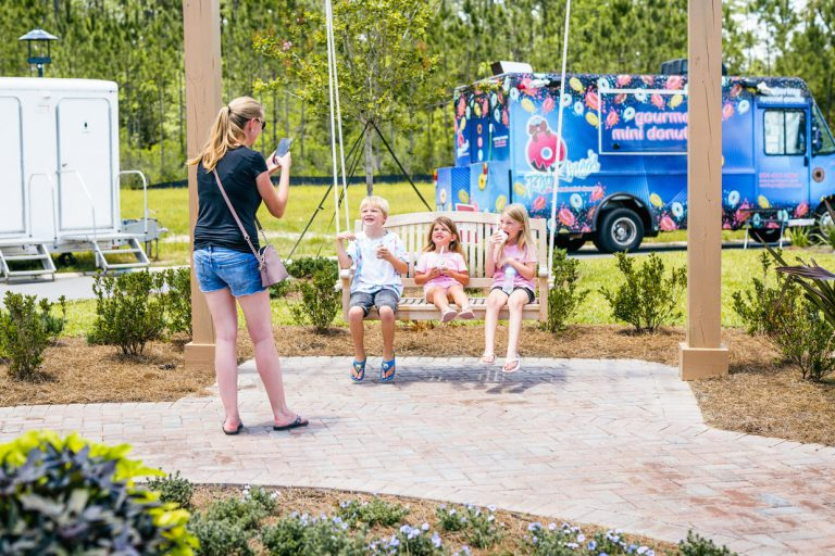 3 kids smiling eating ice cream at Tributary Model Home Event