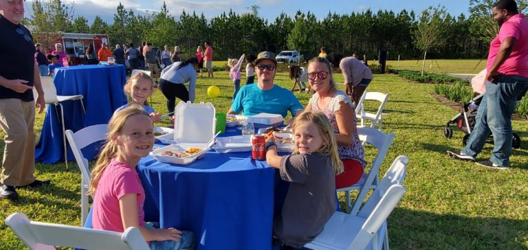 family at table enjoying food smiling at tributary homeowners event