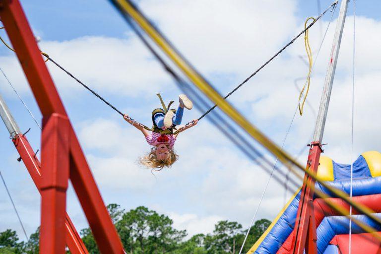 little girl upside down on sling shot at Tributary Model Home Event