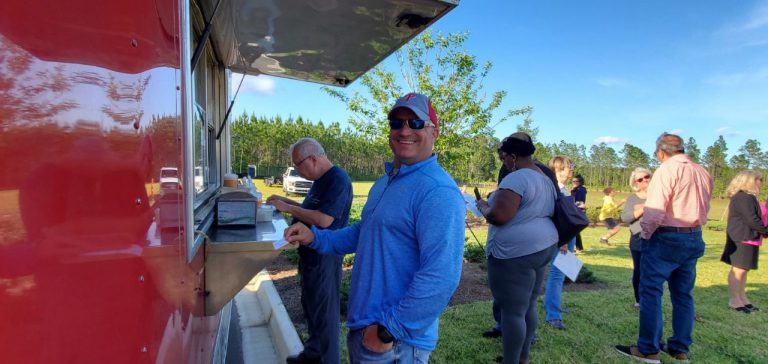 man smiling at food truck at tributary homeowners event