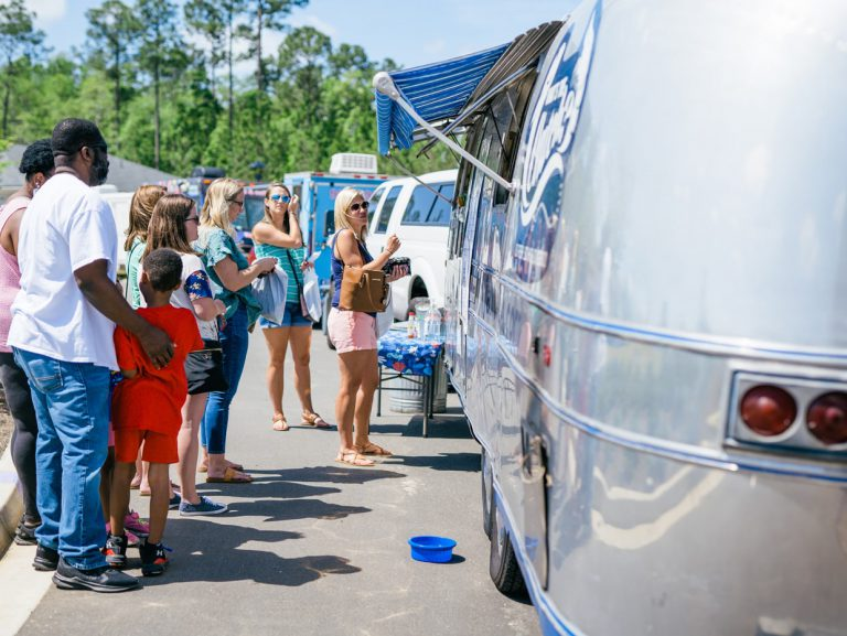people lined up at food truck at Tributary Model Home Event