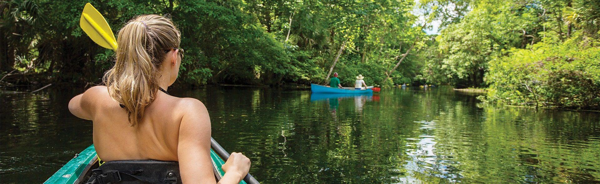 woman kayaking down the nassau river near tributary